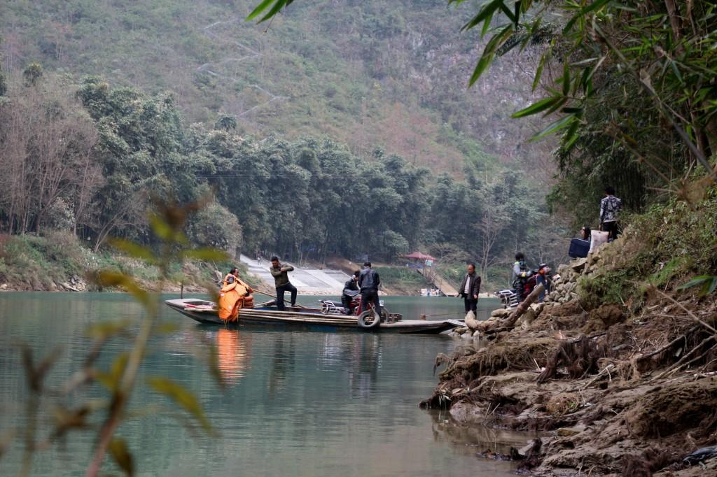 La petite barque qui transporte les grimpeurs et les villageois souhaitant se rendre sur l'autre rive. En arrière plan, on aperçoit le début en zigzag de l'escalier sans fin